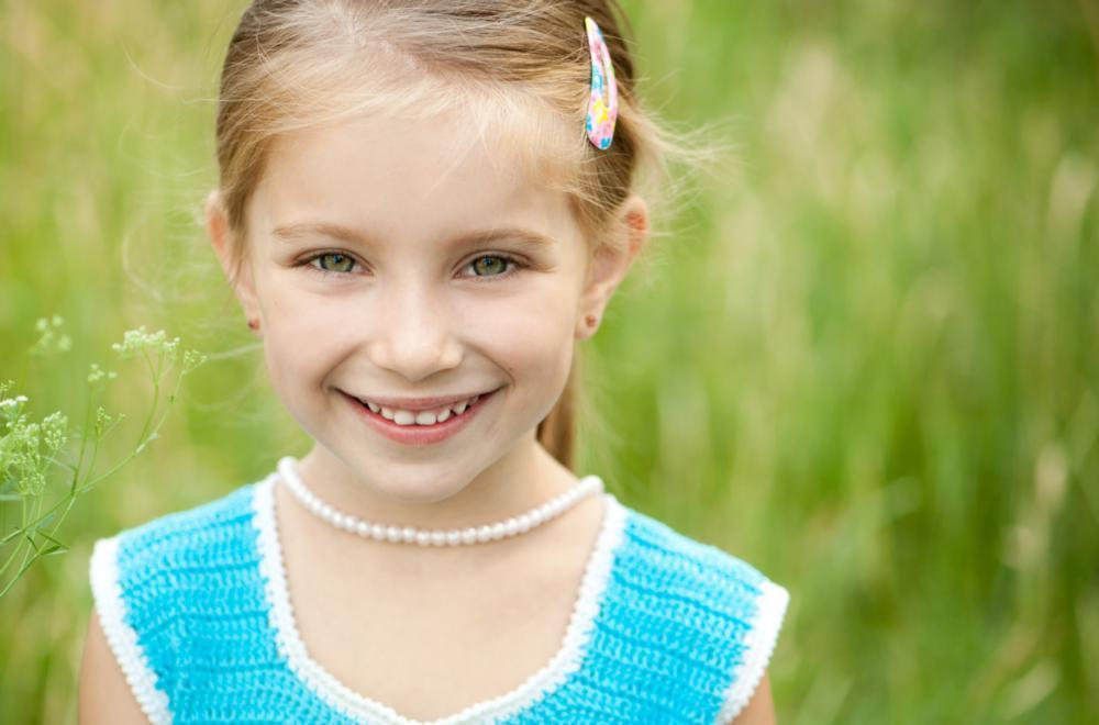 child smiling in grass | dentist aurora il