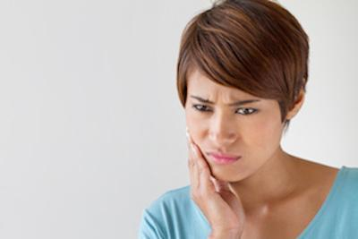 woman holding jaw | Dentist Aurora IL