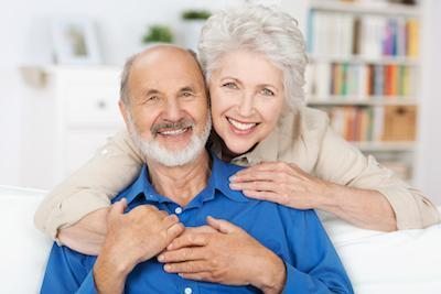 older couple smiling on couch | dentist aurora il