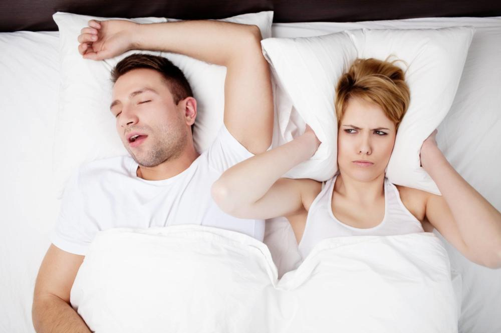 Woman closing ears from partner snoring | Dentist aurora il