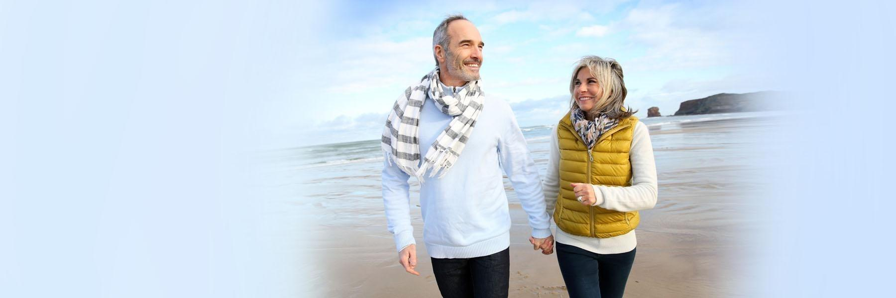 Older couple walking on beach | Dentist Aurora IL